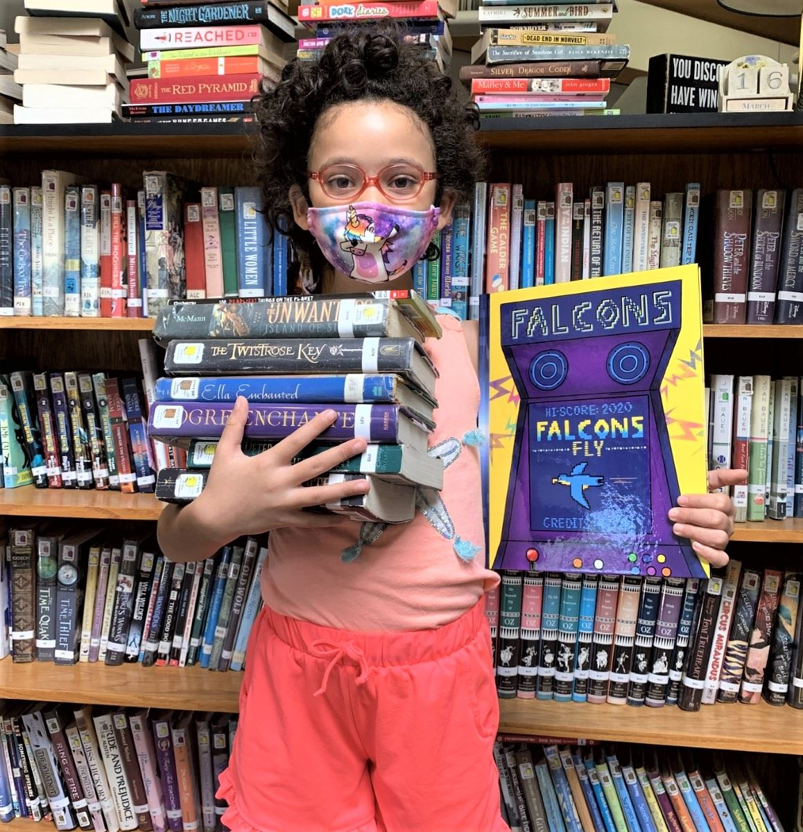 Girl with mask and a stack of books in a library